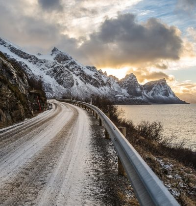 Norwegian landscape with a tiny road along the seaside in a fjord in the winter, Nordland, Norway
