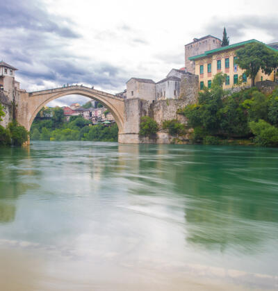 View of the single-arch Old Bridge or Stari Most crossing the Neretva River in Mostar, Bosnia and Herzegovina. The Old Bridge was destroyed on 9 November 1993 by Croat military forces during the Croat–Bosniak War. The area is a UNESCO World Heritage Site.