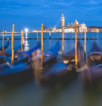 Romantic colorful night view on the lagoon of Venice at sunset during blue hour with moving gondolas and San Giorgio Maggiore church and campanile in the background
