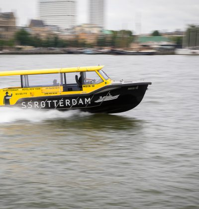 Rotterdam, The Netherlands - September 18, 2016: dynamic image of a Watertaxi sailing on the Nieuwe Maas canal from Wilhelminapier with modern cityscape in the background.