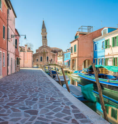 Typical canal with colorful facades with vibrant colors and Church of San Martino and its leaning campanile in famous fishermen village on the island of Burano, Venice, Italy