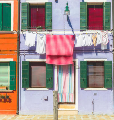 Colorful facades with vibrant colors and laundry drying in famous fishermen village on the island of Burano, Venice, Italy