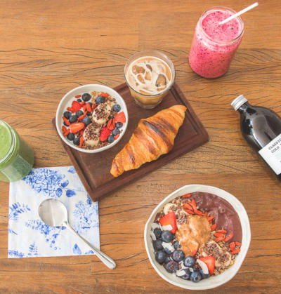 on location food photography with a healthy breakfast board with a croissant, ice coffee and yoghurt muesli bowl, smoothie and acai bowl
