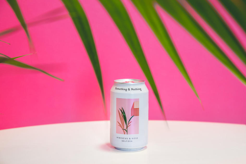 on location food photography with healthy natural can drink with plant and pink background