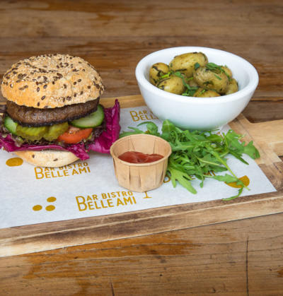on-location food photography with a juicy burger with roasted potatoes, ketchup and rucola salad