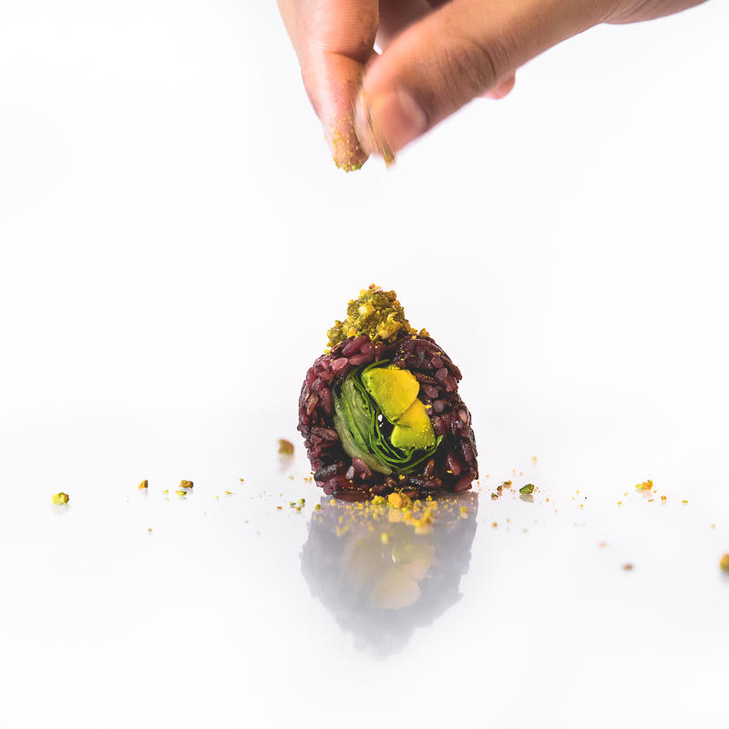 on location food photography with vegan sushi on a white background and a hand sprinkling some pistachios, Vegan Sushi Bar Amsterdam